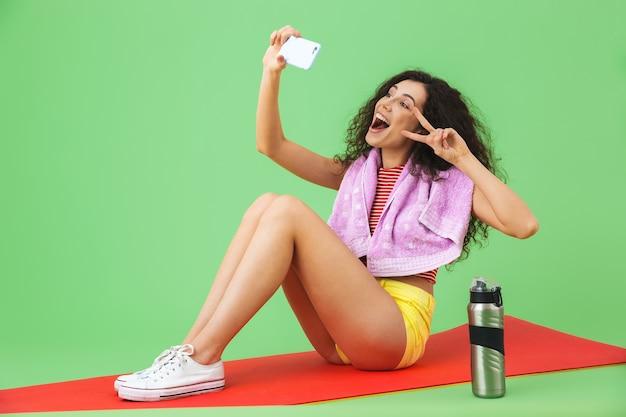녹색 벽에서 운동한 후 피트니스 매트에 앉아 셀카 사진을 찍는 목에 수건을 두른 운동복을 입은 활기찬 20대 여성의 초상화