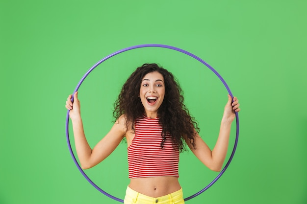 Портрет энергичной женщины 20 лет в летней одежде, делающей упражнения с обручем во время гимнастики на зеленой стене