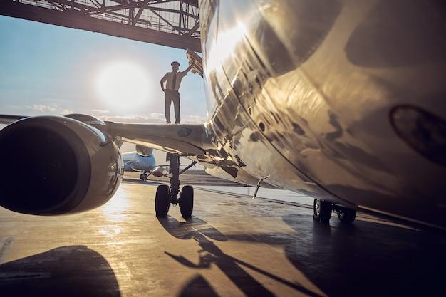 Портрет двигателя коммерческого самолета в аэропорту, пока пилот стоит на крыле, изолированном на солнечном фоне