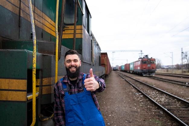 Портрет машиниста паровоза стоит у локомотива на вокзале и показывает палец вверх