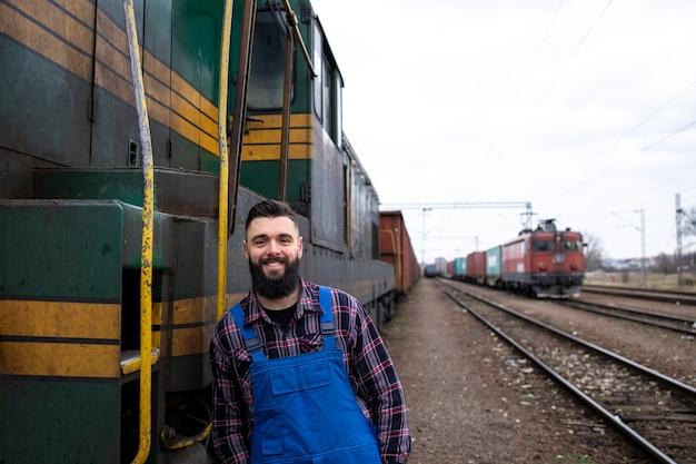 Портрет машиниста паровоза, стоящего у локомотива на вокзале, готового к отправлению.