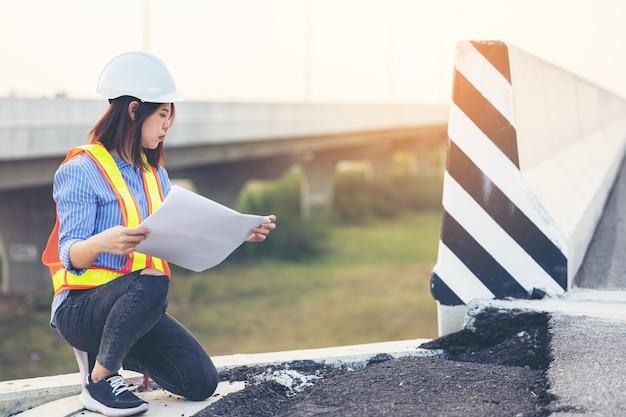 損傷した道路を身振りで示すエンジニアの肖像画、建設を検査する道路労働者
