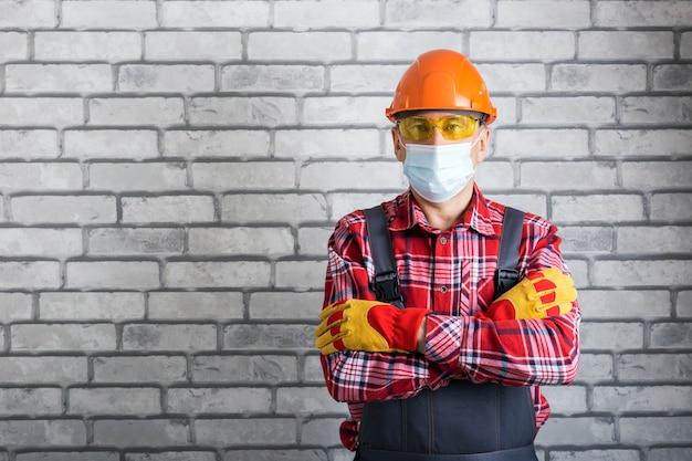 Портрет инженера или рабочего в защитной маске возле backgroun кирпичной стены с копией пространства.