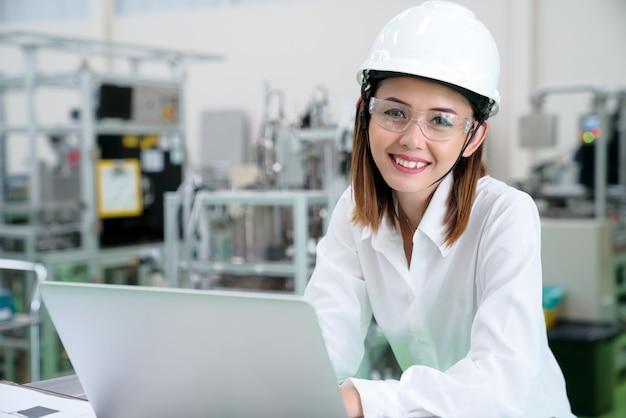 생산 라인의 진행에 대한 노트북과 엔지니어 미소의 초상화는 작업을 수행