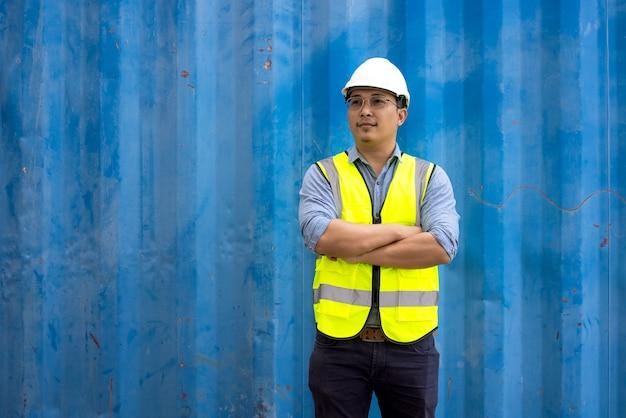 工業用コンテナに制服の安全スーツとヘルメットを身に着けているエンジニアリングの男の肖像画。