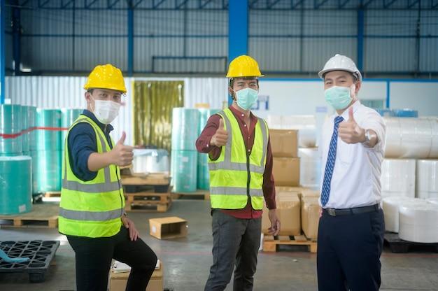 Портрет инженеров в медицинской маске, защитный шлем, работающих на складской фабрике