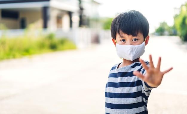 행복한 어린 아시아 소년의 초상화는 집을 떠나기 전에 사회적 거리를 두고 코로나바이러스를 격리하기 위해 보호용 안전 마스크를 쓴 covid19를 중지합니다.