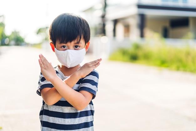 집을 떠나기 전에 사회적 거리를 두고 코로나바이러스를 격리하기 위해 보호용 안전 마스크를 쓴 행복한 어린 아시아 소년의 초상화 프리미엄 사진