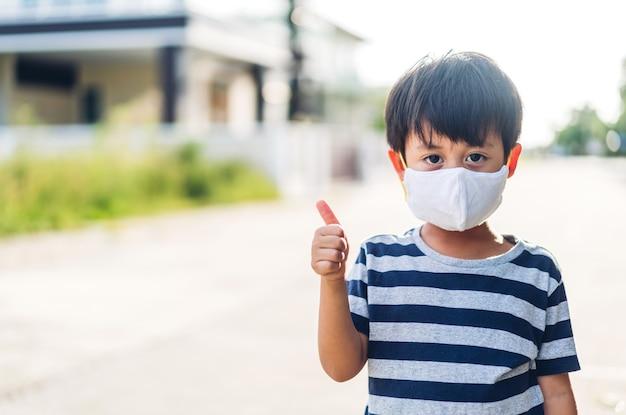 집을 떠나기 전에 사회적 거리를 두고 코로나바이러스를 격리하기 위해 보호용 안전 마스크를 쓴 행복한 어린 아시아 소년의 초상화