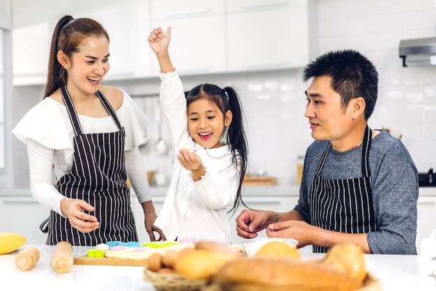 キッチンのテーブルでクッキーやケーキの材料を焼くと一緒に料理を楽しんでいる小さなアジアの女の子の娘の子供と幸せな愛アジアの家族の父と母を楽しむの肖像画