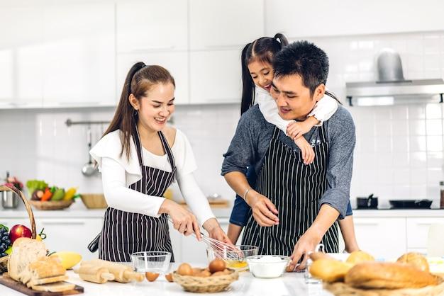 의 초상화는 작은 아시아 여자 딸 아이가 부엌에서 테이블에 쿠키와 케이크 재료를 베이킹 함께 요리 재미와 함께 행복 사랑 아시아 가족 아버지와 어머니를 즐길 수