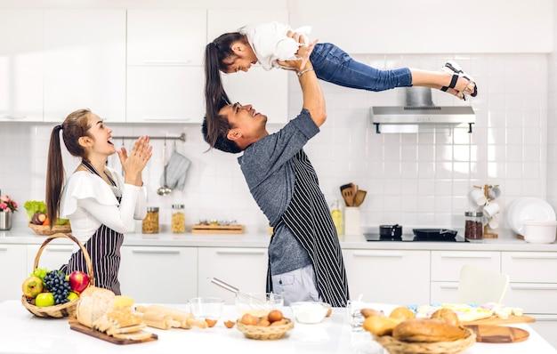 Портрет счастливой любви азиатской семьи, отца и матери с маленькой азиатской дочерью, весело готовящей вместе с выпечкой печенья и ингредиентами для торта на столе на кухне