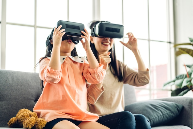 Портрет наслаждаться счастливой любовью азиатской семьи матери и маленького азиатского ребенка девочек, улыбаясь и весело используя очки гарнитуры виртуальной реальности.
