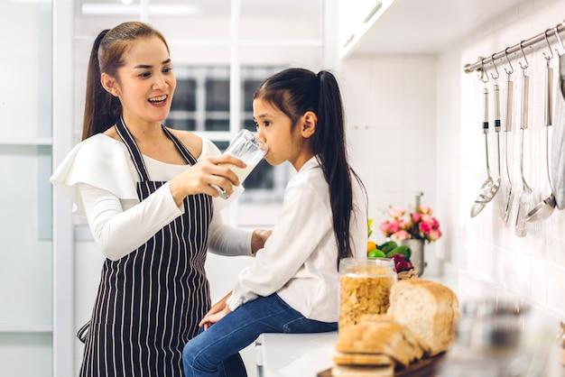 Портрет счастливой любви азиатской семьи, матери и маленькой азиатской дочери, ребенка, улыбающегося и завтракающего, пьющего и держащего стаканы молока за столом на кухне