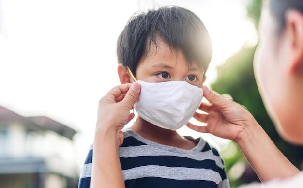 Портрет наслаждающейся счастливой любовью азиатской матери в защитной маске для маленького азиатского мальчика-сына в карантине из-за коронавируса с социальным дистанцированием перед выходом из дома