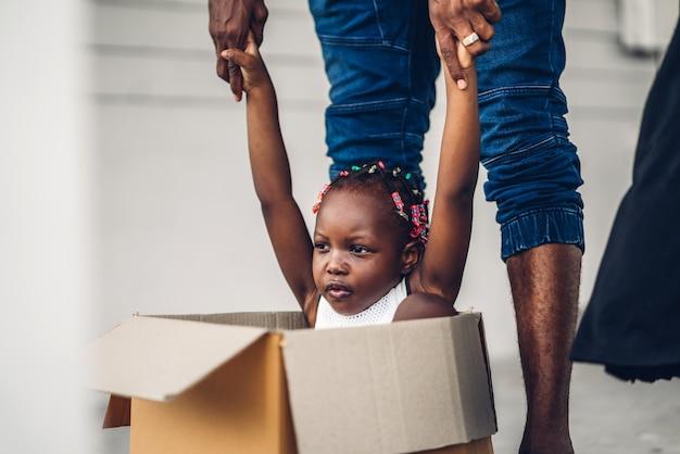 幸せな愛を楽しむ黒家族アフリカ系アメリカ人の父と段ボール箱に座っている小さなアフリカの女の子の肖像画