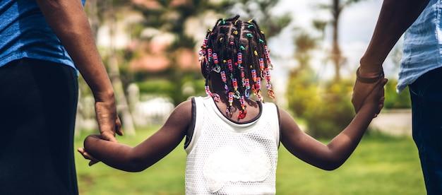 幸せな愛を楽しむ黒家族アフリカ系アメリカ人の父と母の家で夏の公園での良い時間の瞬間に小さなアフリカの女の子の手を握って