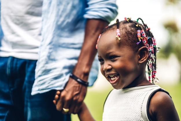 夏の公園で楽しい時間の瞬間に小さなアフリカの女の子の手を握って幸せな愛黒家族アフリカ系アメリカ人の父を楽しむの肖像画