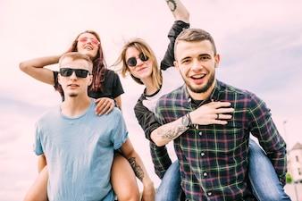 Portrait of enjoyable friends against blue sky