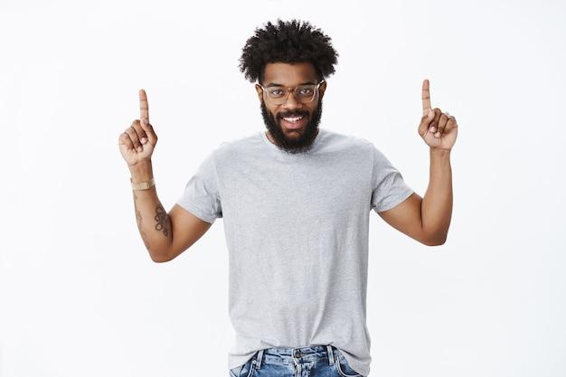 Портрет восторженного привлекательного счастливого молодого афро-американского мужчины с вьющимися волосами, татуировками и пирсингом в носу, поднимающим руки вверх, указывая вверх и улыбаясь