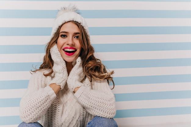 Портрет восторженной, эмоциональной дамы в удобной мягкой теплой одежде и зимних аксессуарах, сидящей на полу у сине-белой стены