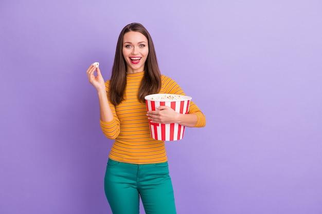 Портрет восторженной девушки у зимних выходных, в большой полосатой коробке с поп-корн, наслаждайтесь просмотром смешных сериалов, носите стильный джемпер, стильный образ жизни, изолированный на фиолетовом цвете