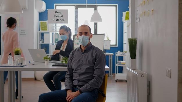 コロナウイルスのパンデミックに対する保護フェイスマスクを身に着けている起業家の男の肖像画。営業所のテーブルデスクで働く従業員は、ウイルスの病気を防ぐために社会的距離を維持します