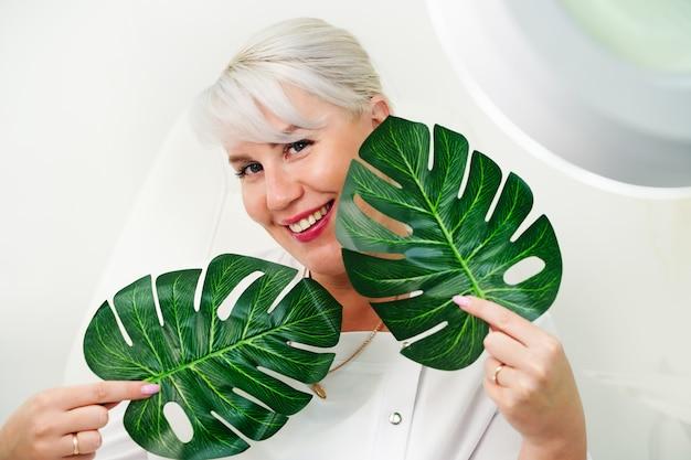 緑のモンステラを保持している新鮮な健康な肌を持つヨーロッパの美しい若い女性のブロンドの髪の肖像画...