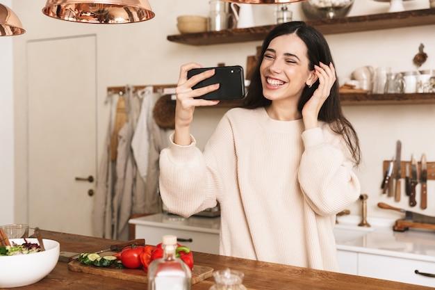 집에서 세련된 주방에서 야채와 함께 그린 샐러드를 요리하는 동안 스마트 폰에서 셀카 사진을 복용 유럽 갈색 머리 여자의 초상화