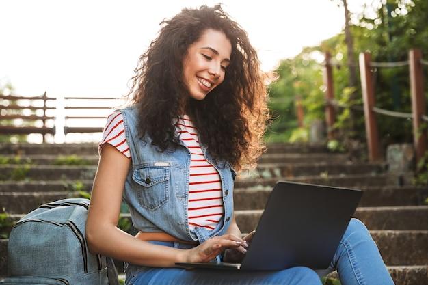 夏の日に公園の階段に座って、銀のラップトップを使用して笑顔でヨーロッパのブルネットの女性の肖像画