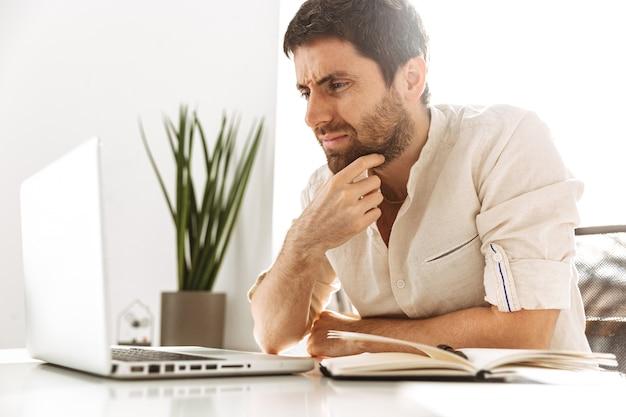 Портрет европейского делового мужчины 30-х годов в белой рубашке, работающего с ноутбуком и бумажными документами, сидя в ярком офисе