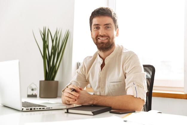明るいオフィスに座っている間、ラップトップで作業している白いシャツを着ているヨーロッパの実業家30代の肖像画