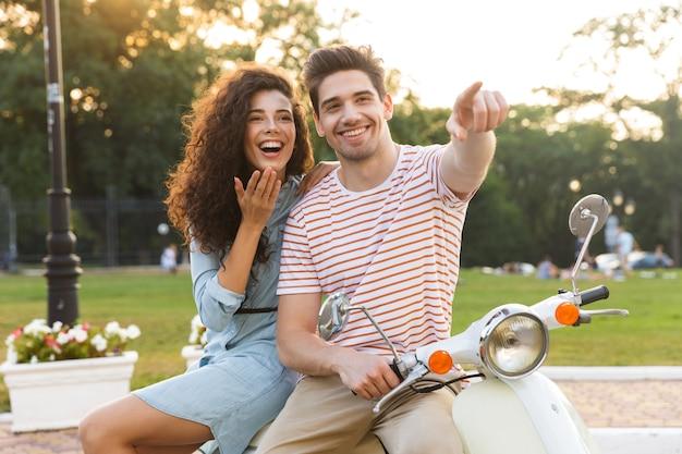 都市公園でバイクに一緒に座って、ヨーロッパのカップルの肖像画