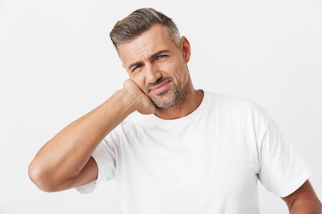 カジュアルなtシャツを着て頬に触れ、白で隔離された歯痛に苦しんでいる剛毛を持つ30代のヨーロッパ人の肖像画
