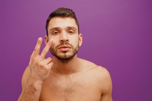 Портрет европейца нанести косметический крем на лицо. сосредоточенный молодой бородатый парень смотрит в камеру. концепция ухода за кожей лица. изолированные на фиолетовом фоне. студийная съемка. копировать пространство
