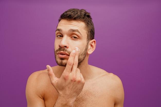 Портрет европейца нанести косметический крем на лицо. сосредоточенный молодой бородатый парень, глядя на камеру. концепция ухода за кожей лица. изолированные на фиолетовом фоне. студийная съемка. копировать пространство