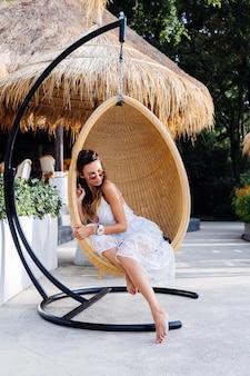 Портрет европейской романтичной женщины в белом летнем платье вне курортного отеля в стуле соломы яйца.