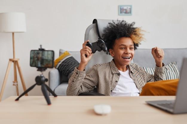 自宅でビデオゲームやオンラインストリーミング、若いゲーマーやブロガーのコンセプト、コピースペースをプレイしながら応援している興奮したアフリカ系アメリカ人の少年の肖像画