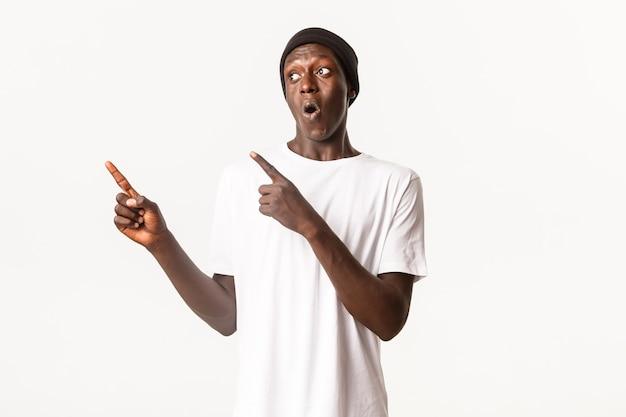 Портрет взволнованного и довольного афро-американского парня в шапочке, указывающего пальцами и смотрящего влево с заинтригованным выражением лица