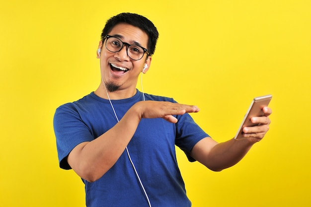 Портрет возбужденного азиатского мужчины, счастливо смеющегося, слушая музыку со смартфона, изолированного на желтом фоне