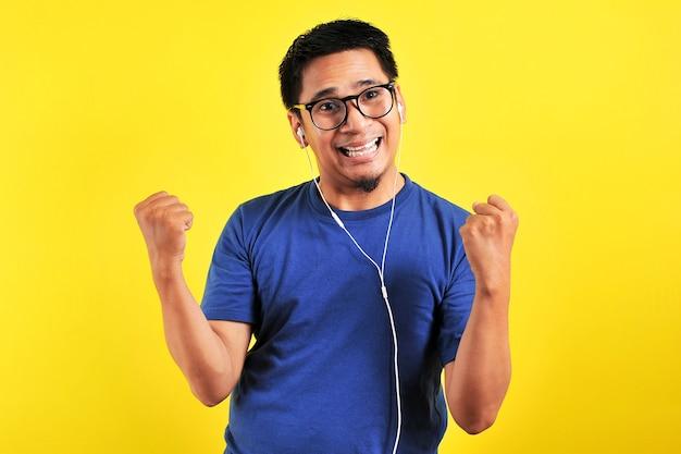 Портрет возбужденного азиатского мужчины, радостно смеющегося, слушая музыку со смартфона