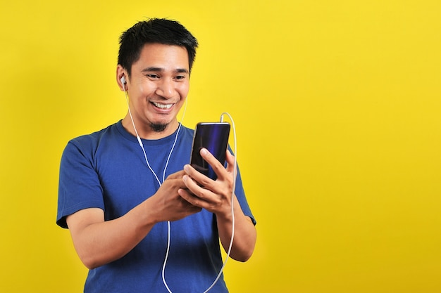 Портрет возбужденного азиатского мужчины удивлен, обнаружив в сети популярную песню