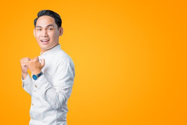 成功した表情の白いシャツを着た興奮したアジア人の男性のポートレート