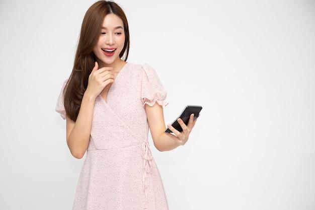 Портрет возбужденной азиатской женщины, держащей калькулятор, изолированные на белом фоне.