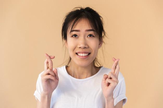 スタジオでベージュの壁に分離された指を交差させて幸運を願って基本的なtシャツを着て興奮しているアジアの女性の肖像画