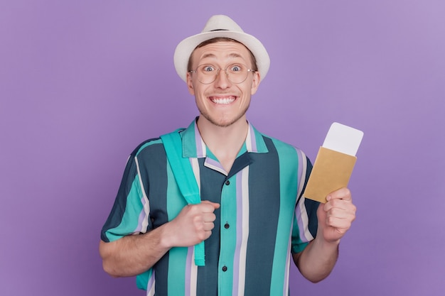 흥분한 놀란 만족한 남자의 초상화는 보라색 배경에 티켓 문서 비자를 들고 있다