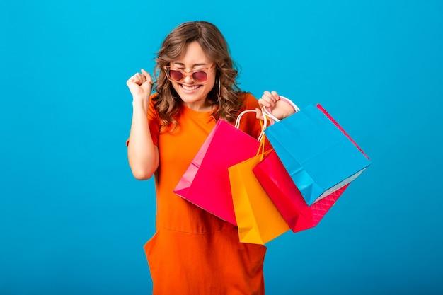 Портрет возбужденной привлекательной улыбающейся стильной женщины-шопоголика в оранжевом модном платье, держащей сумки на синем фоне студии