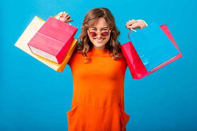 고립 된 블루 스튜디오 배경에 쇼핑백을 들고 오렌지 유행 드레스에 흥분된 매력적인 미소 세련 된 여자 쇼핑의 초상화