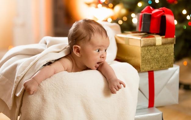 Портрет взволнованного мальчика, смотрящего на стопку рождественских подарков