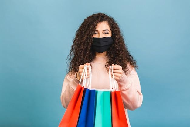 Портрет возбужденной красивой кудрявой девушки в медицинской защитной маске на лице, держащей хозяйственные сумки, изолированные на розовом фоне